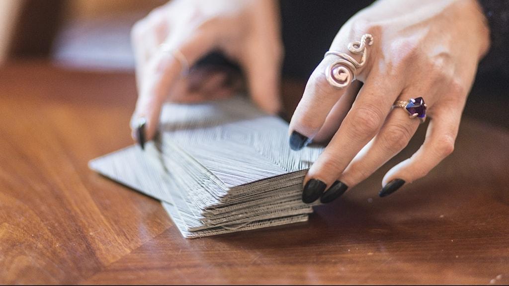 Händer håller i tarotkort.
