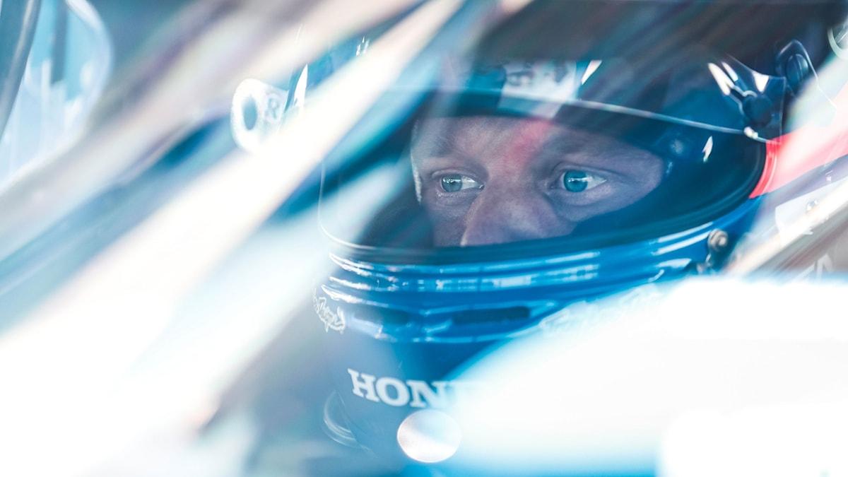 Racingförare tittar ut från sin hjälm.