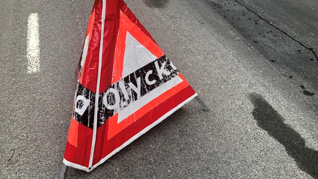 """En bild på en rödvit kon med texten """"Olycka"""" på, placerad vid kanten på en asfaltsväg."""