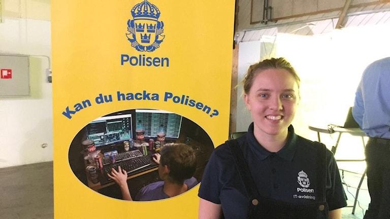 """Kvinna framför gul poster med texten """"Kan du hacka polisen?"""""""