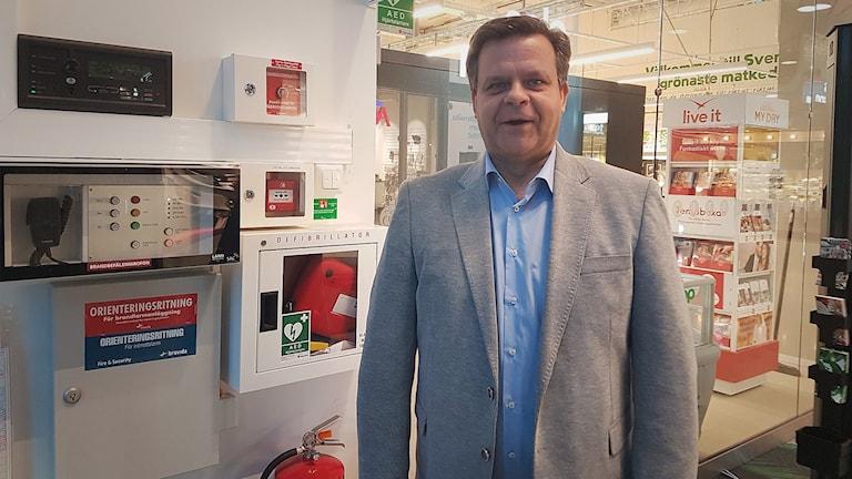 Lars Bröms står bredvid en brandsläckare och annan brandutrustning.