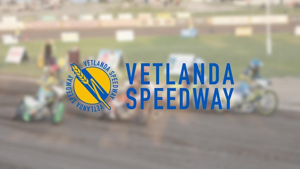 Suddig bild från speedwaymatch, i förgrunden logga med texten Vetlanda speedway.