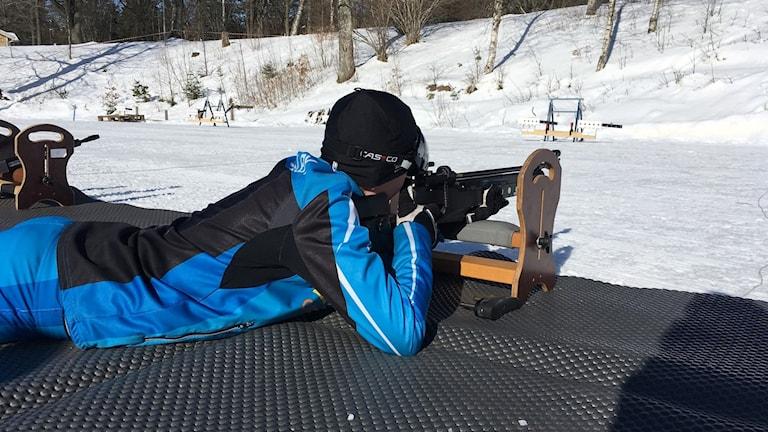 En kille i blå skiddräkt ligger och skjuter på skidskyttebanan.