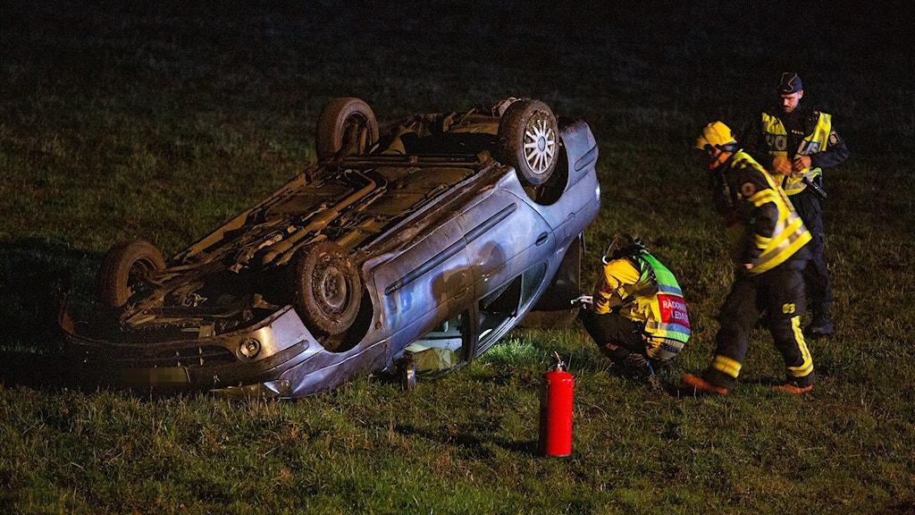 Mörk bil ligger upp-och-ner på grön gräsmatta. Två personer från räddningstjänst med gula jackor och en polis med reflexväst står intill bilen på gräsmattan.