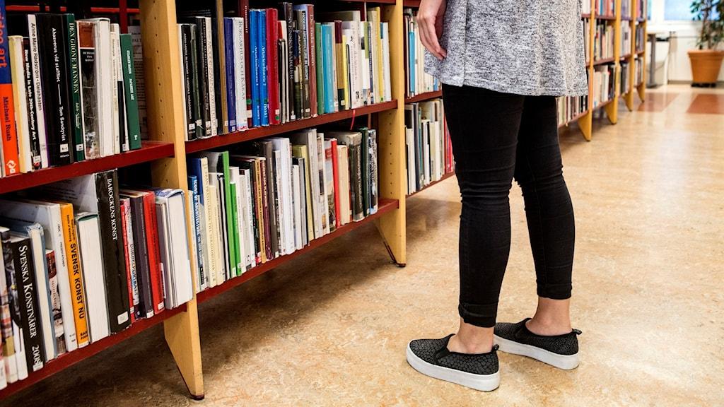En person står vid bokhyllor på ett bibliotek.
