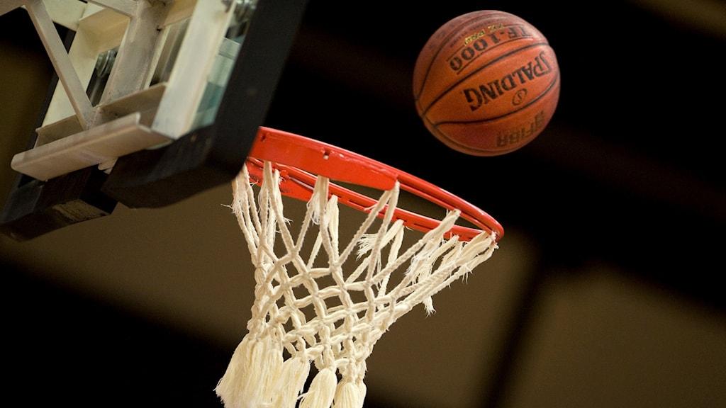 Basketboll faller genom nät.