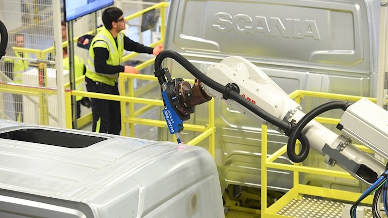 En man arbetar med en lastbil för Scania.