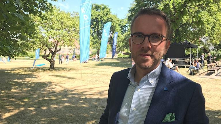 Man i blå kavaj och glasögon i utamhusmiljö. I bakgrunden blåa flaggor med Kristdemokraternas logotyp.