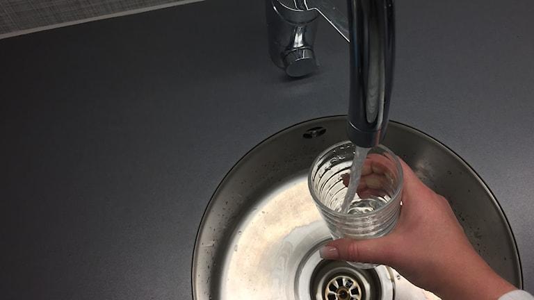 En hand som håller i ett glas under en rinnande kran.