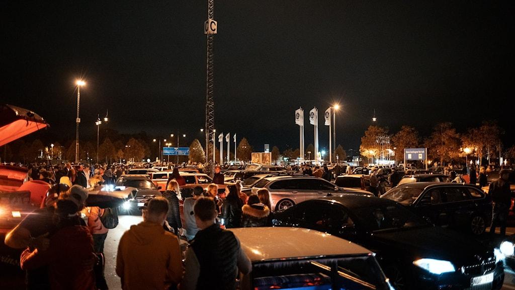 Mörkt ute. Fullt av bilar och människor på stor parkeringsplats. Vimmel.