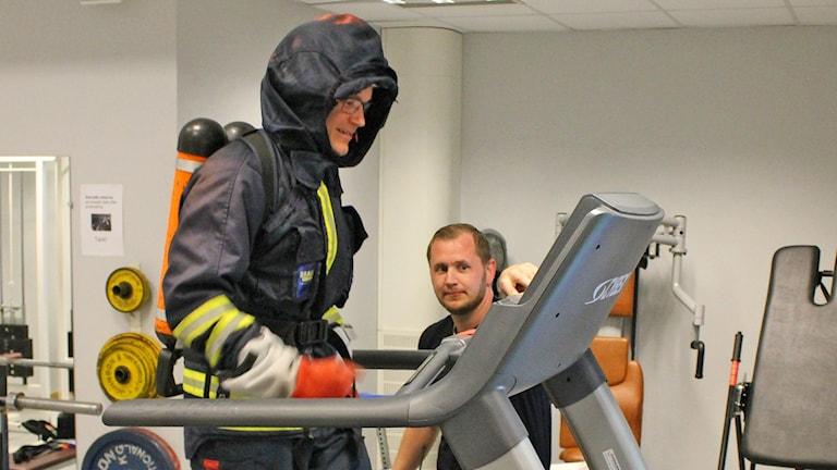 Mattias Rang i rökdykardräkt på ett löpband och Andreas Karlsson bredvid