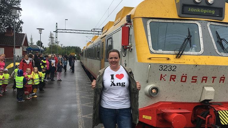 Kvinna med vit t-shirt där det står I love Äng står framför ett parkerat passagerartåg vid välfylld men regnig tågperrong.