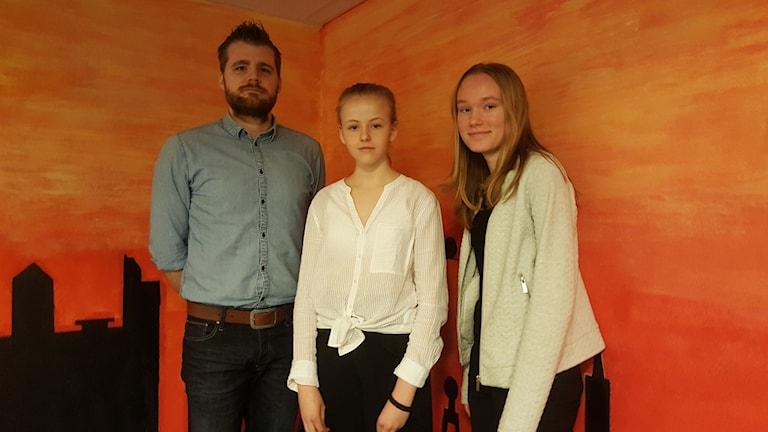 Rickard Boson står bredvid Cornelia och Ella framför en orange vägg.