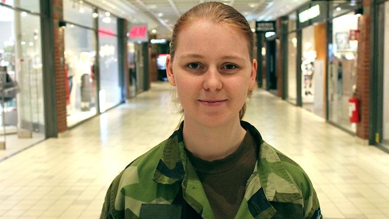 Felicia Olsson står i sina militärkläder i mitten av en gång på A6.