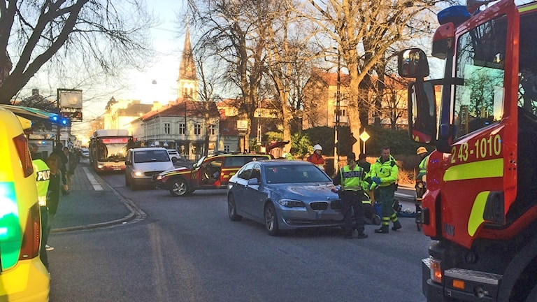 Brandbilar och räddningspersonal vid en bil.