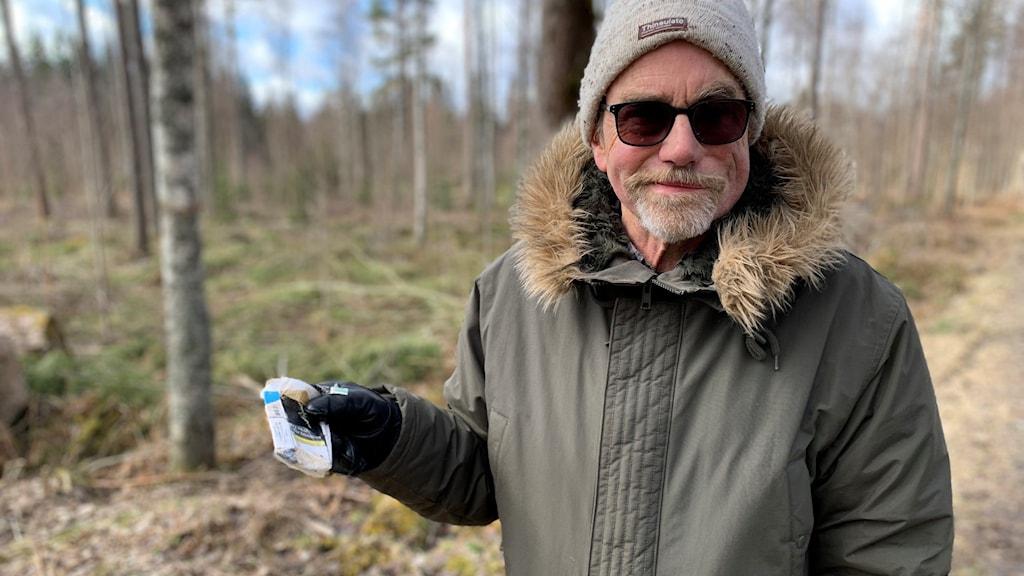 Lars Lindfors med ett cigarettpaket som han hittat i skogen.