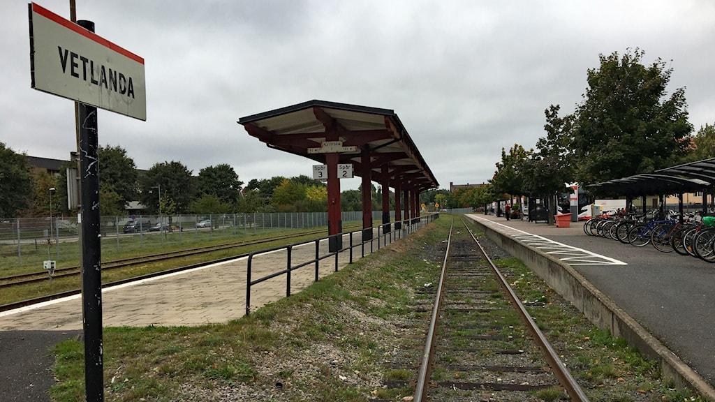 """En tom järnvägsstation med en perrong under tak mellan spåren. En stationsskylt har texten """"Vetlanda""""."""