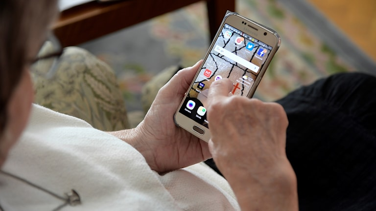 En äldre kvinna använder en smartphone.