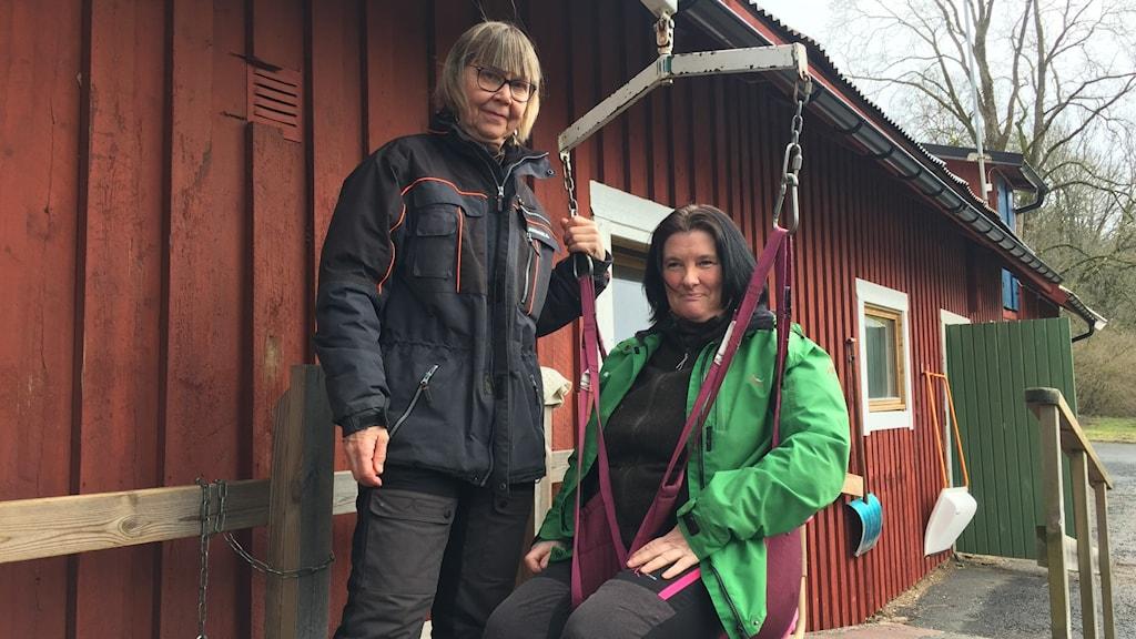 Annika Sterner Andréasson står bredvid Sara Xavier som sitter i den lift som hjälper en rullstolsburen person upp på hästryggen.