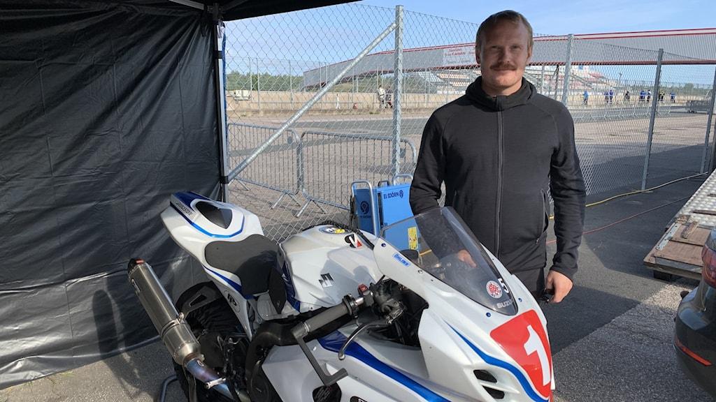 Bild på Viktor med sin vita stora motorcykel.