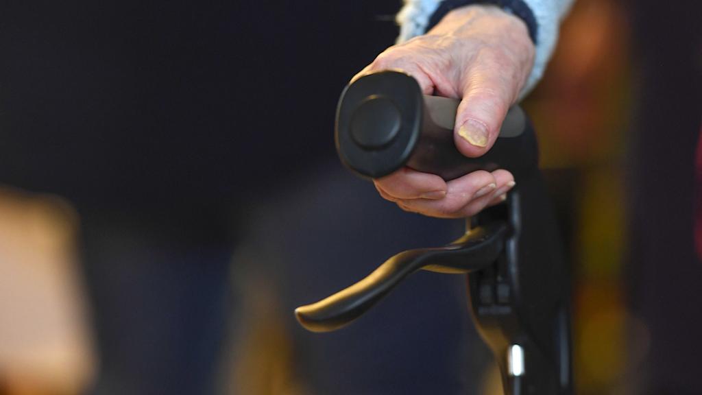 Genrebild. Närbild på en äldre persons hand på en rullator.