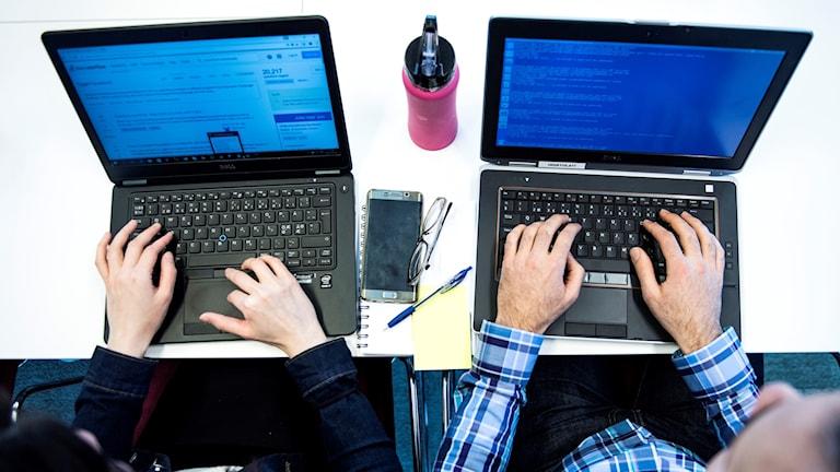 Bild ovanifrån på två personer som sitter vid varsin dator.