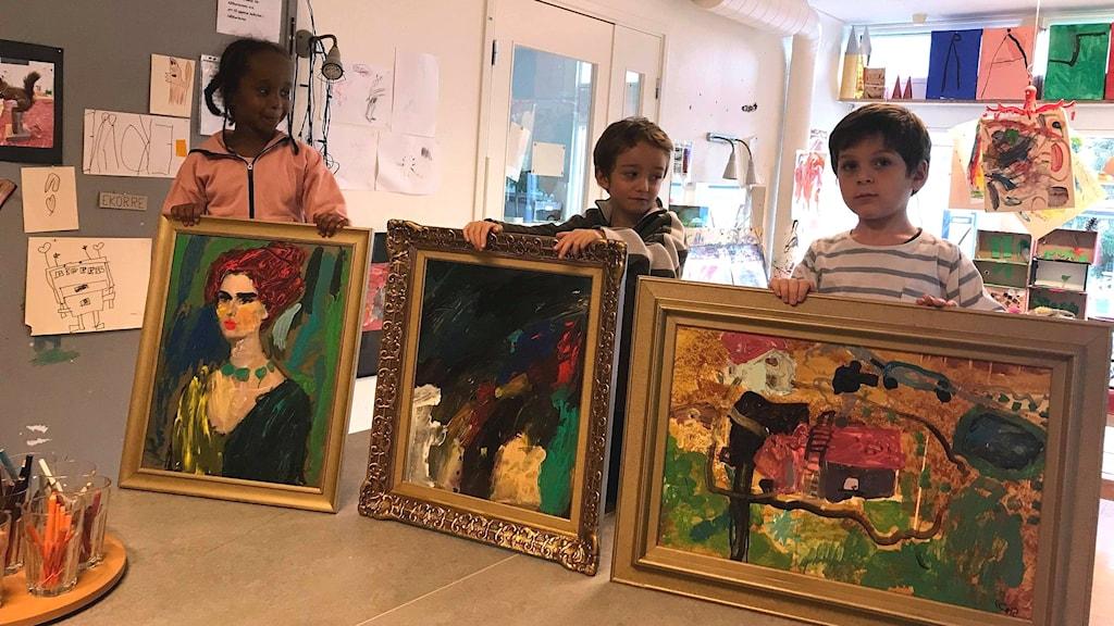 Tre barn med varsin tavla som de målat för Världens barn.