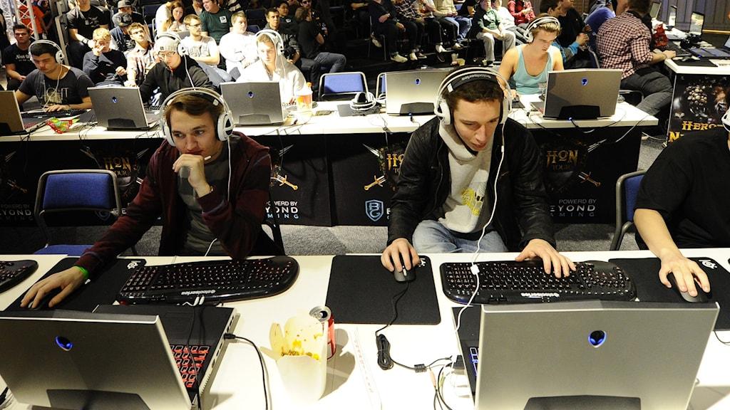 Flera personer spelar datorspel, personer i bakgrunden tittar på.