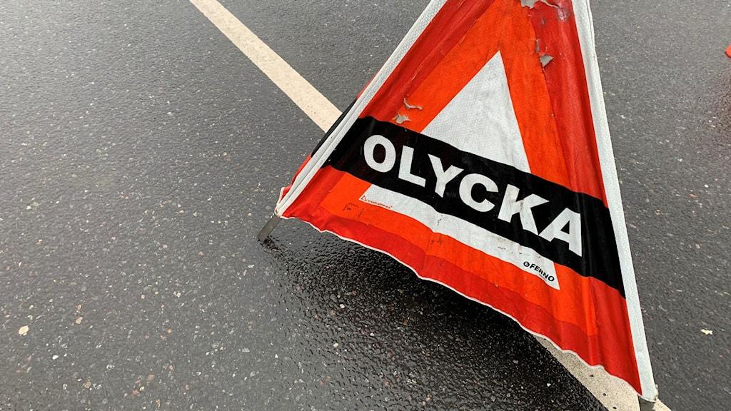 """En orange, röd och vit kon med texten """"olycka"""" på placerad på en bar asfaltsväg."""