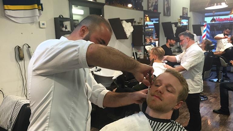 HV-spelaren Ted Brithén sitter i en frisörstol och får sitt skägg trimmat.