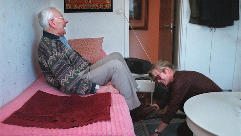 En kvinna dammsuger under en säng medan en äldre man sitter på sängen och ser glad ut.
