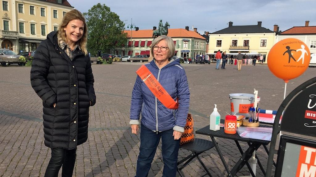 Sophie Carlo och Anita Delavaux, Eksjö handel, står på torg i Eksjö med Världens barn-artiklar.
