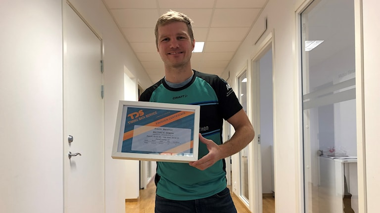 Mattias håller i ett inramat diplom.