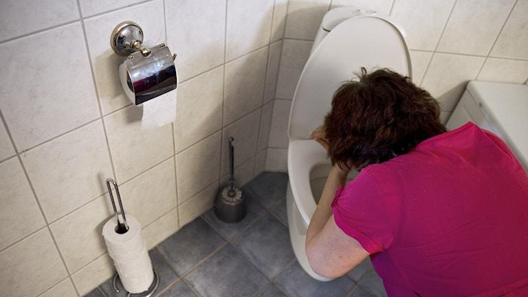 En kvinna hänger över en toalettstol.