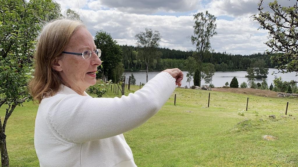 EN kvinna pekar ner mot en sjö