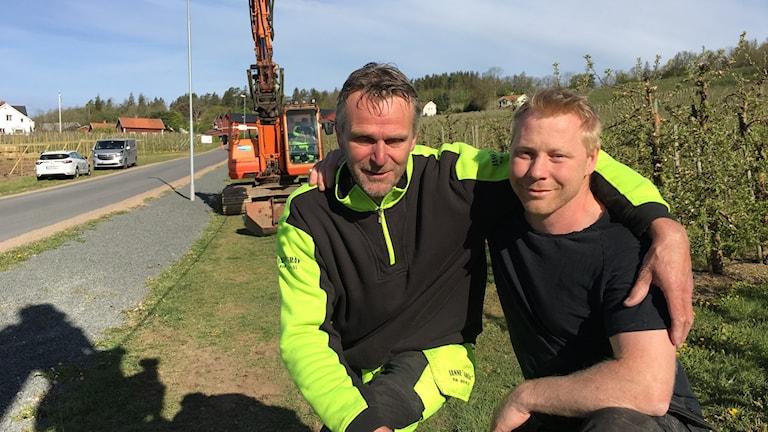 Två män utomhus på landet framför en grävmaskin.