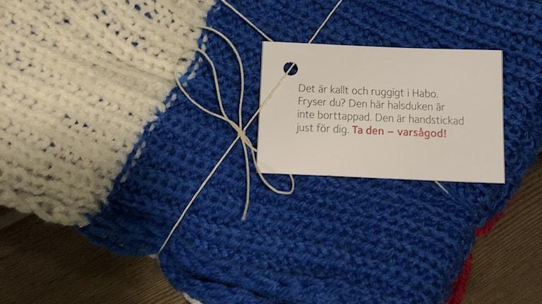 """En stickad vit och blå halsduk ihopvikt och knuten med snöre. På en lapp står texten """"Det är kallt och ruggigt i Habo. Fryser du? Den här halsduken är inte borttappad. Den är handstickad just för dig. Ta den -- varsågod!""""."""