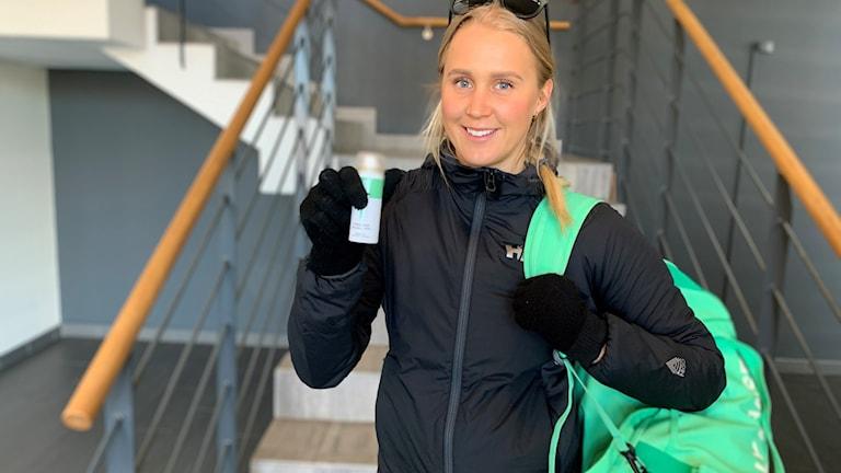 Emelie Wikström med handsprit och träningskläder.