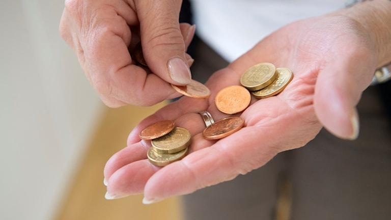 Händer med mynt i. Foto: Henrik Montgomery/TT.