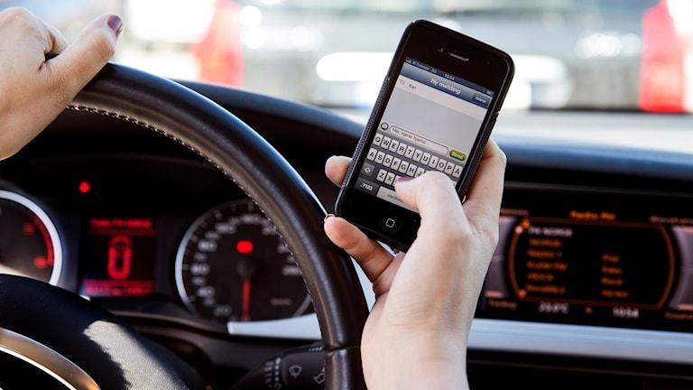 En person smsar på en mobiltelefon samtidigt som hen kör.