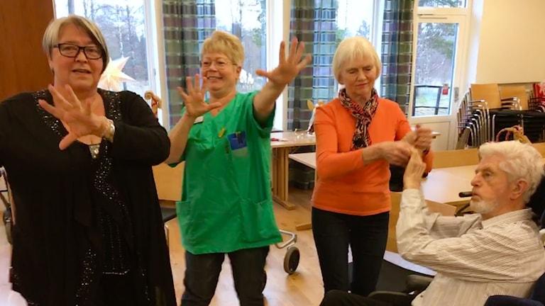 Tre kvinnor står upp och dansar, en man sitter i en rullstol och håller en av kvinnorna i händerna.