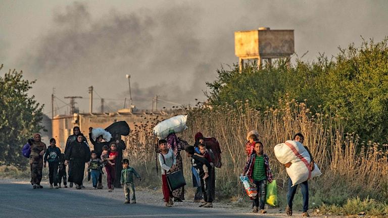 Civila som flyr den syriska staden Ras al-Ain utmed den turkiska gränsen 9 oktober 2019.