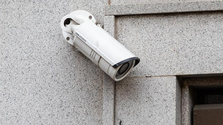 En vit övervakningskamera på en ljusgrå stenvägg.