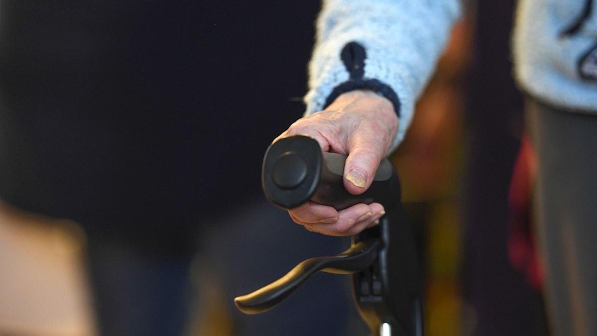 Detaljbild på äldre man med rollator.