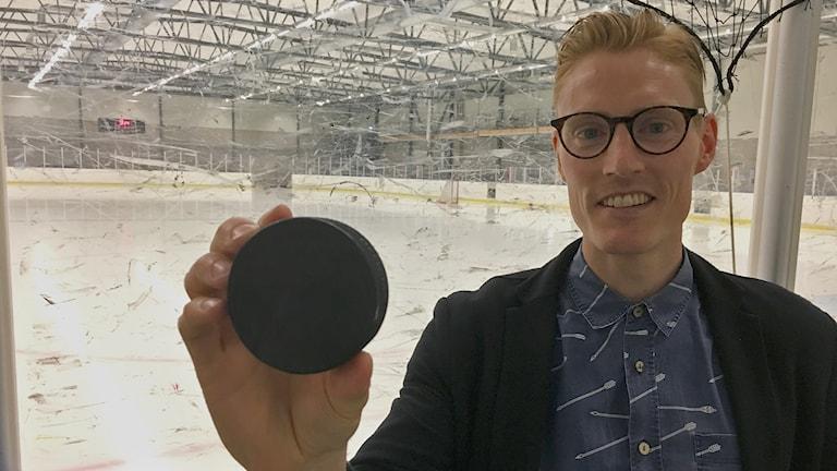 Martin Funck står vid en hockeyrink och håller upp en puck mot kameran.