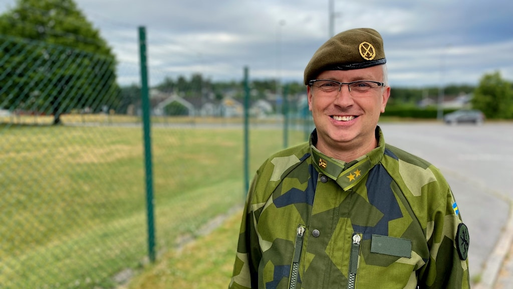 En man i militära kläder står vid ett stängsel.