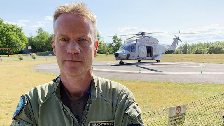 En man i grön flygdräkt står framför en grå helikopter