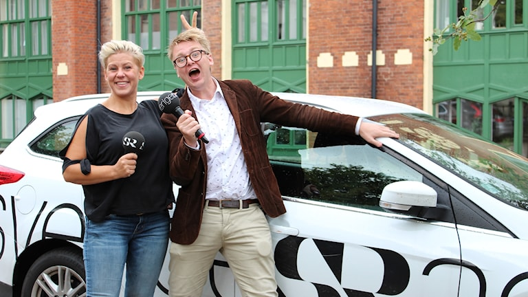 Sanna och Malte står glada framför Sveriges Radios bil.