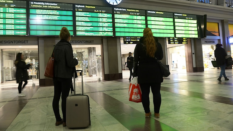 Två kvinnor tittar på informationsskyltar om avgångar på en tågstation.