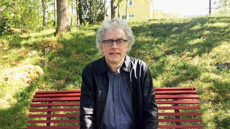 En man i sitter mitt på en röd bänk i en grön park.